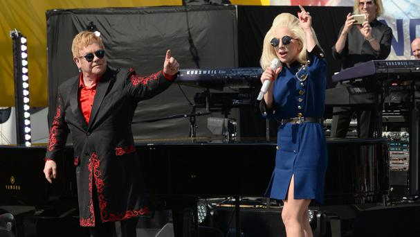 Sir Elton John and Lady Gaga salute fans at a surprise concert on Sunset Strip (Invision/AP)