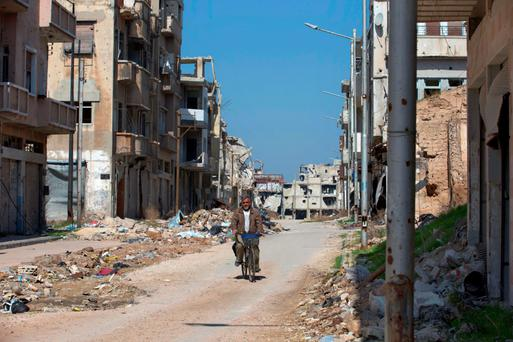 A man rides a bicycle through a devastated quarter of the old city of Homs, Syria, over the weekend. Photo: Hassan Ammar