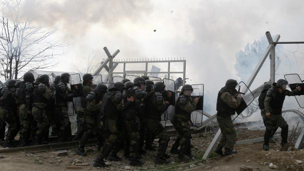 Stranded refugees and migrants break an iron fence and throw stones from the Greek side of the border as Macedonian police use tear gas, near the southern Macedonian town of Gevgelija (AP)