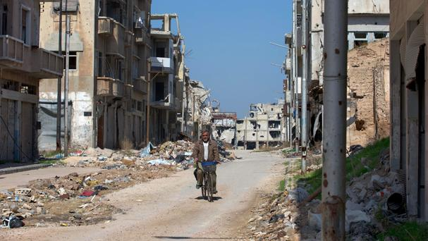 A Syrian man rides a bicycle through a devastated part of the city of Homs (AP)