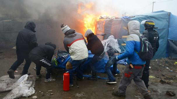 Migrants and activists clear a tent away from a fire in the Calais migrant camp