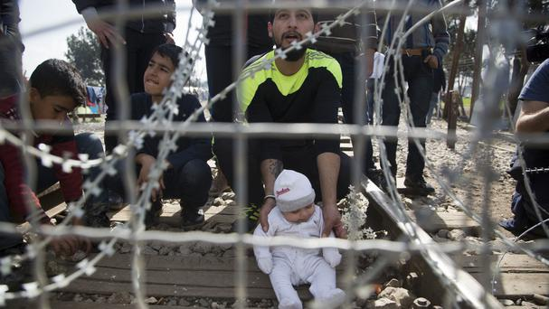 A migrant father with his child waits on the Greek side of the border to enter Macedonia (AP)