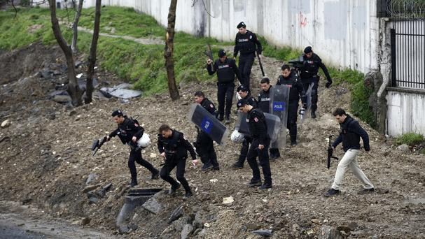 Security forces run to surround the area during an operation against two attackers in Bayrampasa, Istanbul (AP)