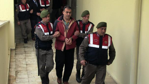Turkish paramilitary police escort Syrian smugglers Muwafaka Alabash, front, and Asem Alfrhad, rear, at the trial in Bodrum (AP)