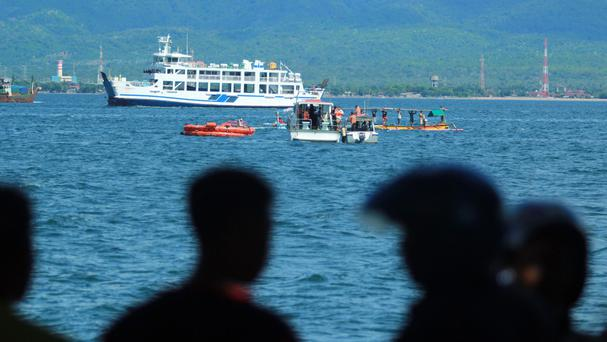 Residents watch as rescuers search for survivors off Banyuwangi, East Java (AP)