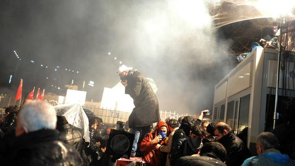 Riot police fire tear gas and use water cannons on crowds outside the headquarters of Zaman newspaper in Istanbul (AP)