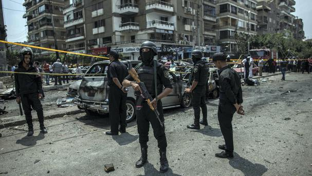 Egyptian police officers stand guard at the site of a bombing that killed Egypt's top prosecutor, Hisham Barakat, in Cairo (AP)
