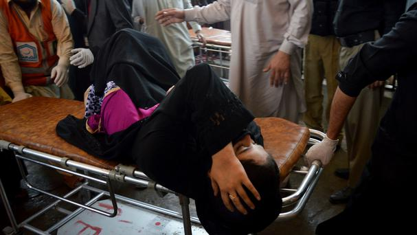 Volunteers rush an injured woman to a hospital in Peshawar, Pakistan, following the bomb attack. (AP)