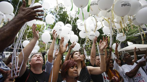 Relatives of passengers and crew of the ill-fated Malaysia Airlines Flight 370 release balloons with the names of those who were on board during a commemorative event in Kuala Lumpur, Malaysia (AP)