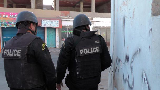 Tunisian police officers take positions during clashes with militants in Ben Guerdane (AP)