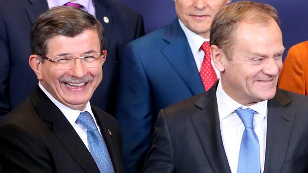 European Council President Donald Tusk, front right, shakes hands with Turkish Prime Minister Ahmet Davutoglu at the EU summit in Brussels (AP)