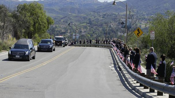 Ronald Reagan Presidential Library volunteers line the road as Nancy Reagan's body arrives (AP)