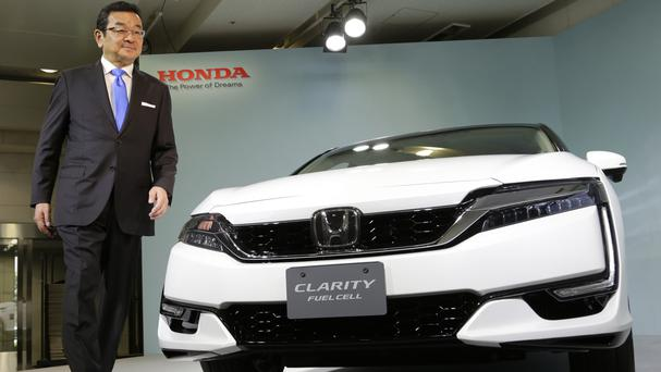 Honda president and chief executive Takahiro Hachigo shows off the Clarity fuel cell at the car maker's headquarters in Tokyo (AP)