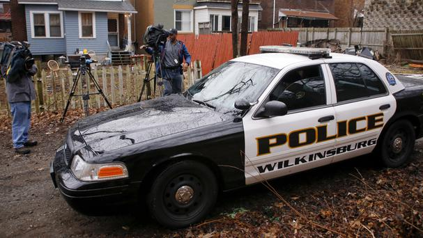 Police drive past the scene of the deadly shooting (AP)