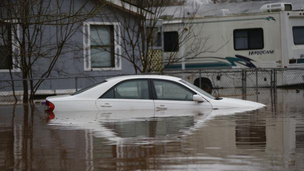 A car is seen partially submerged during rising floodwater in Louisiana (AP)
