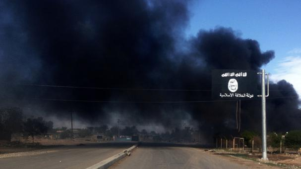Smoke billows behind an Islamic State sign during clashes between militants from IS and Iraqi security forces (AP)