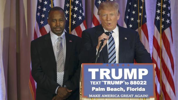 Ben Carson listens to Donald Trump during a news conference in Palm Beach, Florida Credit: AP