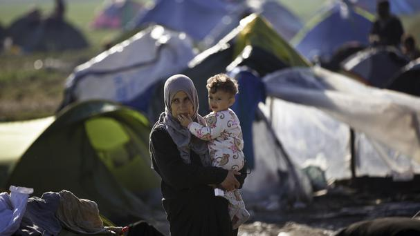 A migrant mother holds her child at the northern Greek border station of Idomeni (AP)