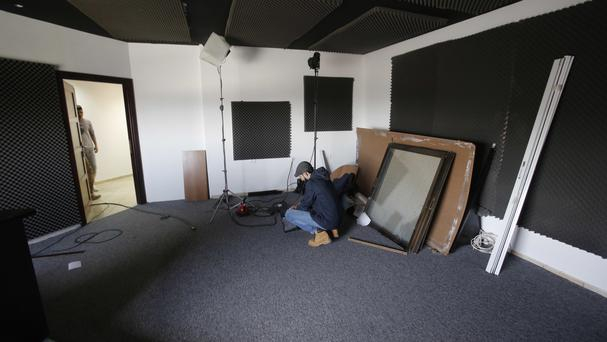 An employee of the Falestine al-Youm TV station inspects damaged equipment after an Israeli raid (AP)