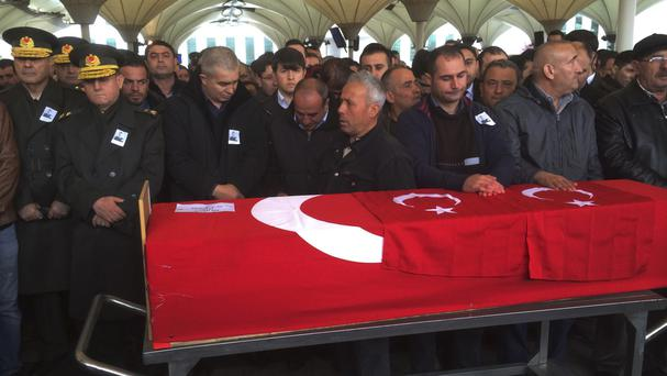People stand by the Turkish flag-draped coffin of Murat Gul, 20, a security agent killed in Sunday's explosion in Ankara (APP)