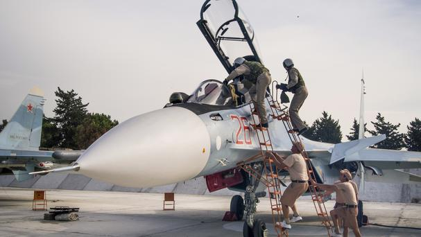 Russian air force pilots climb into their fighter jet at the Hemeimeem base in Syria (AP)