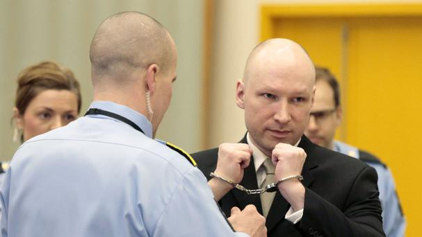 Anders Behring Breivik has his handcuffs removed inside a court room at Skien prison in Skien, Norway (Lise Aserud/NTB scanpix via AP)