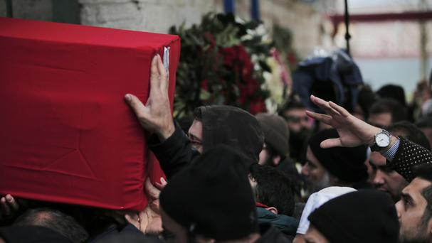 A man reaches out as mourners carry a Turkish flag-draped coffin following Sunday's explosion in Ankara (AP)
