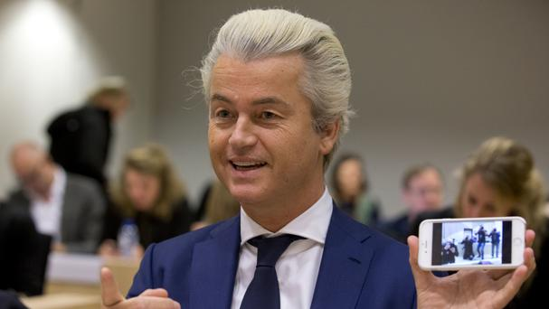 Geert Wilders shows a picture he took of the photographers as he appeared in court for a pretrial hearing at a high-security court on charges of inciting hatred, in Amsterdam (AP)