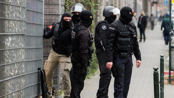 Police officers guard an entrance of a school during a raid in the Molenbeek neighbourhood of Brussels (AP)