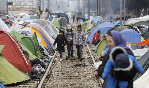 NATIONS UNDER CANVAS: Refugee children walk along railway tracks at a makeshift migrant camp in the northern Greek border post of Idomeni. Photo: Boris Grdanoski