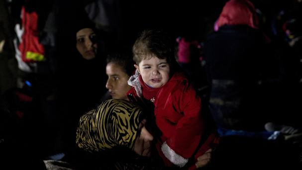 A child cries as she and her family arrived in the northeastern Greek island of Lesbos (AP)