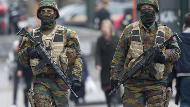 Belgian soldiers patrol outside a Brussels court building where Salah Abdeslam, the top suspect in last year's deadly Paris attacks, was expected to appear before a judge (AP)