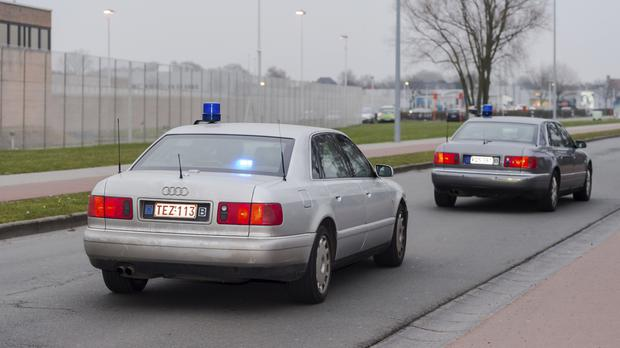 Two police cars, one believed to be transporting terror suspect Salah Abdeslam, leave the prison in Bruges, Belgium, for his court appearance (AP)
