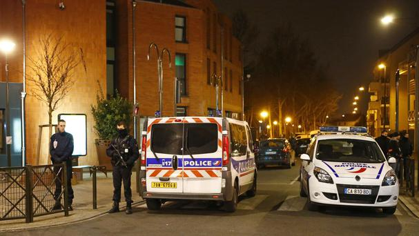 Police seal off a street in Argenteuil as security forces lock down the area during the search (AP)