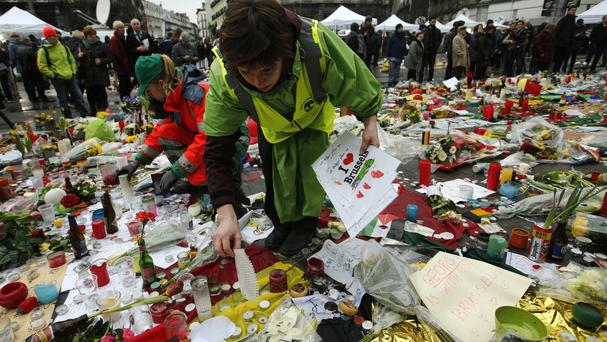 Workers from the City of Brussels gather tributes at one of the memorial sites at the Place de la Bourse in Brussels (AP)