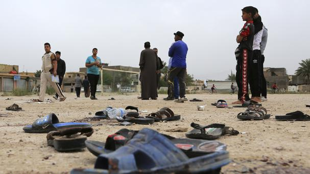 People inspect the aftermath of a suicide bombing at a soccer field in Iskandariya, Iraq (AP)