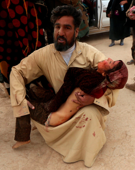 Isil's war crimes: An Iraqi man carries the body of his daughter who died during clashes between Iraqi forces and Isil last week near the city of Mosul Photo: Safin Hamed