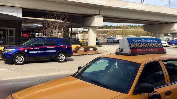 An Atlanta Police rides-for-hire enforcement vehicle sits amid taxi cabs outside the departures area of the domestic terminal at Hartsfield-Jackson Atlanta International Airport (AP)