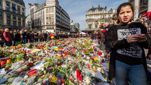 People stop and look at floral tributes at a memorial site at the Place de la Bourse in Brussels