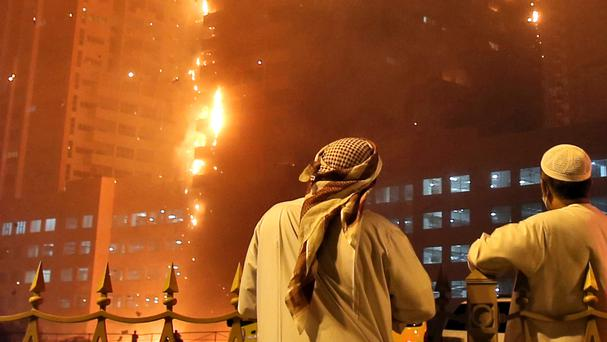 Officials watch as a fire spreads up the side of a high-rise building in Ajman, United Arab Emirates (AP)