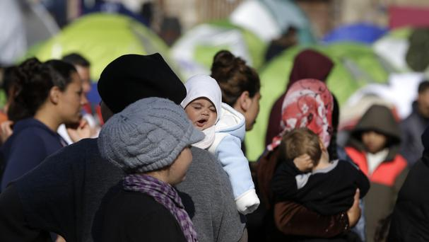 Refugees and migrants queue for food handouts in the Greek port of Piraeus (AP)