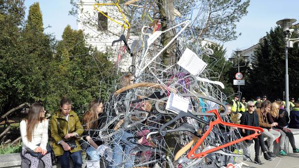 People sit next to a tree covered with hangers, symbolising an illegal abortion, in front of the Polish parliament (AP)