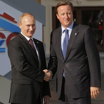 Vladimir Putin shakes hands with David Cameron (AP)