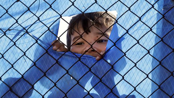 A migrant child looks out behind a wire fence of a refugee camp in the western Athens suburb of Schisto during the first day of the implementation of the deal between EU and Turkey (AP)