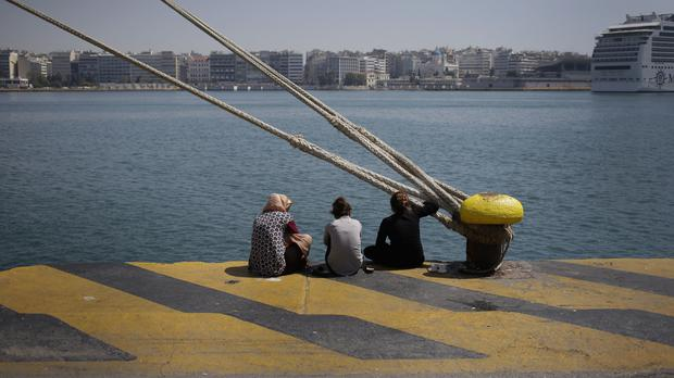 Migrants sit at a promenade of the Athens port of Piraeus (AP)