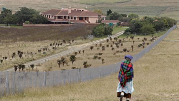 A woman passes the rural home of the late former president Nelson Mandela in Qunu, South Africa (AP)