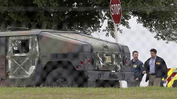 FBI officials walk behind a military vehicle near the scene of the shooting at Joint Base San Antonio-Lackland (John Davenport/San Antonio Express-News/AP)