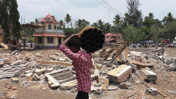 A man walks carrying empty shells of fireworks past a collapsed building after a massive fire broke out during a fireworks display at the Puttingal temple complex in Kerala state, India (AP)