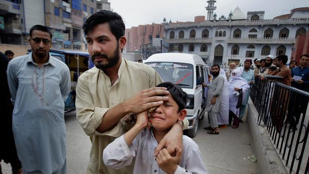 A man helps an injured boy to hospital after an earthquake in Pakistan (AP)