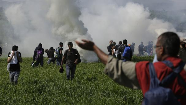 A group of migrant men run away from tear gas used by Macedonian police (AP)